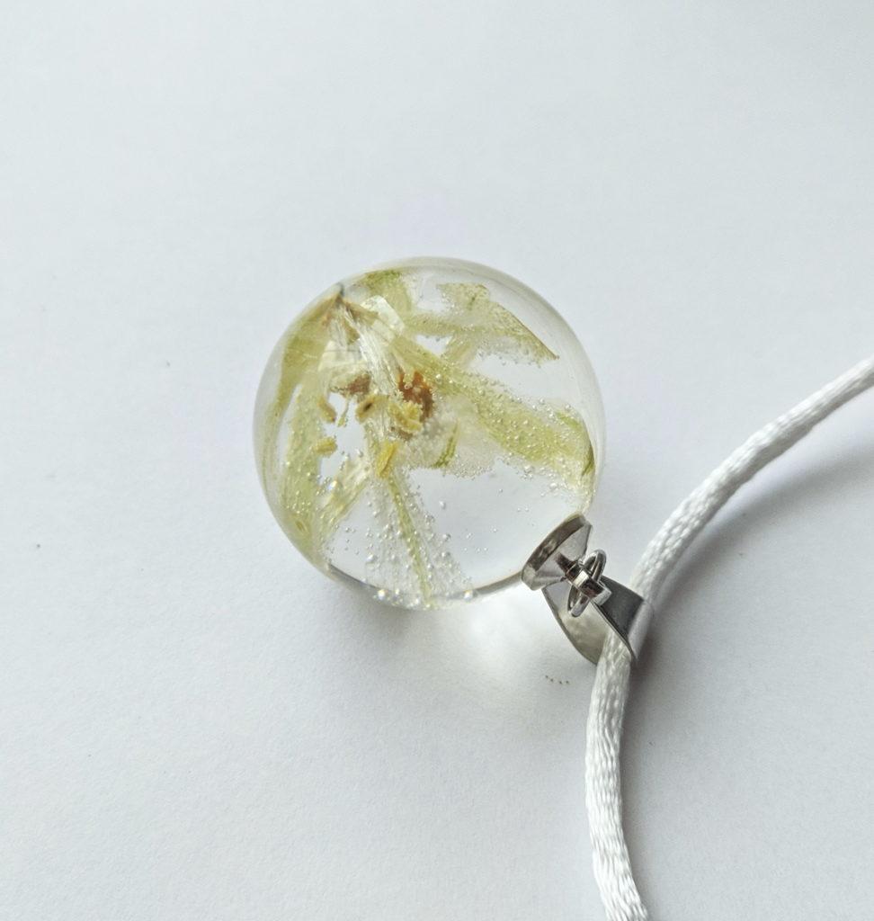 Naszyjnik ze srebrną krawatką. Wiosenny, biały kwiat, zamknięty w żywicznej kuli.