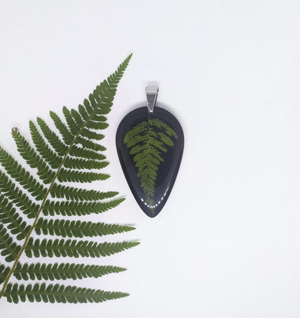 Naszyjnik w kształcie łezki. Czarne tło, z zatopioną naturalną paprocią. Krawatka w kolorze srebrnym